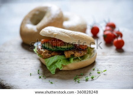 bagel with salad, soy steak, cucumber and tomato slices