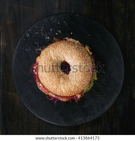 Bagel with salted salmon, spinach, beetroot sprouts, avocado and scrambled egg on wooden chopping board over old wood black background. Top view. Square image