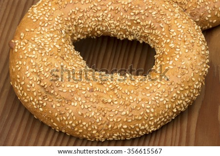 Bagel with sesame seeds on old wooden background.