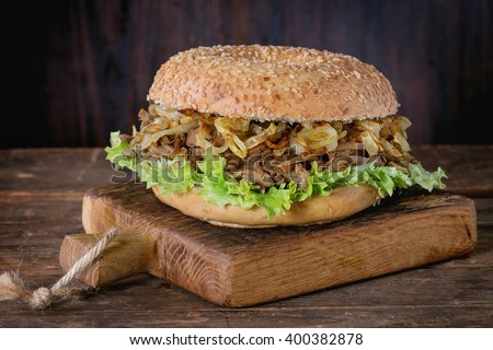Bagel with stew beef, fresh salad and fried onion on small wooden chopping board over wooden background. - stock photo