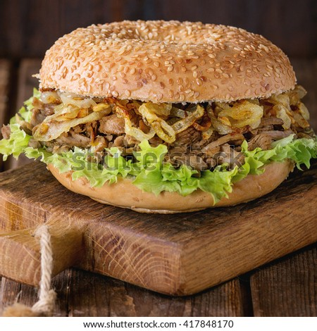 Bagel with stew beef, fresh salad and fried onion on small wooden chopping board over wooden background. Square image - stock photo