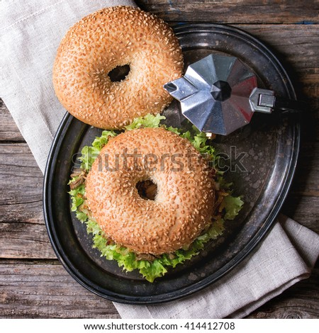 Bagel with stew beef, fresh salad and fried onion served on vintage metal tray with coffee pot over wooden table. Top view. Square image - stock photo