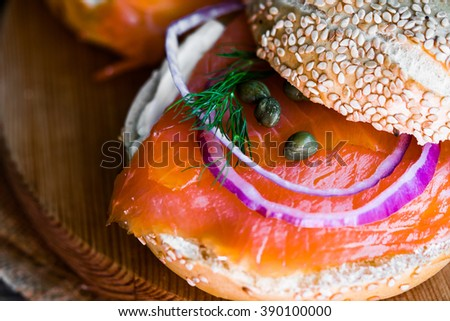 Bagels with cream cheese and smoked salmon on rustic wooden background - stock photo