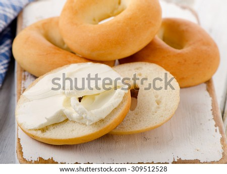 Bagels with cream cheese on  wooden board. Selective focus - stock photo