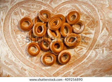 Bagels with flour on wooden background in heart  - stock photo