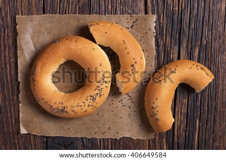 Bagels with poppy seeds on old wooden table, top view - stock photo