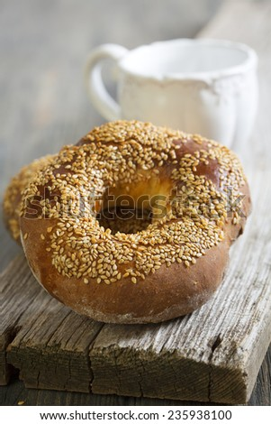 Bagels with sesame seeds on the old board.