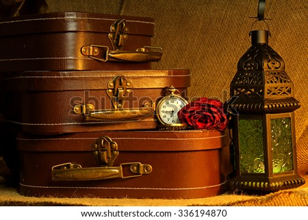 Baggage and a lantern with a pocket watch and a red Rose still life. - stock photo