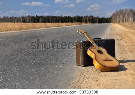 baggage and guitar lies on empty countryside road - stock photo
