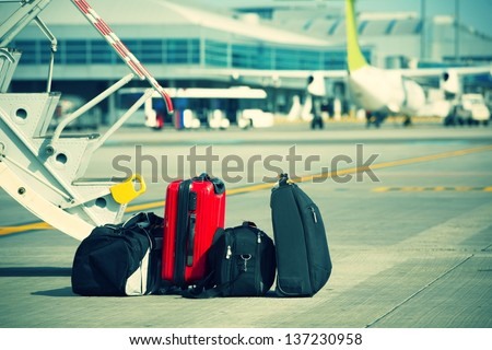 Baggage in front of the airplane - stock photo