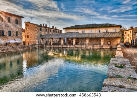 Bagno Vignoni, Siena, Tuscany, Italy: old thermal baths at dawn in the medieval village; vapor over the water in the square of sources, spa basin in the ancient italian town