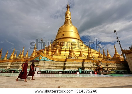 BAGO,MYANMAR - OCT 5: Unidentified buddhist monk walking around Shewemawdaw Paya or Mutao on October 5, 2012 in Bago, Myanmar. It is a sacred and sacred place of tourist and burmese - stock photo