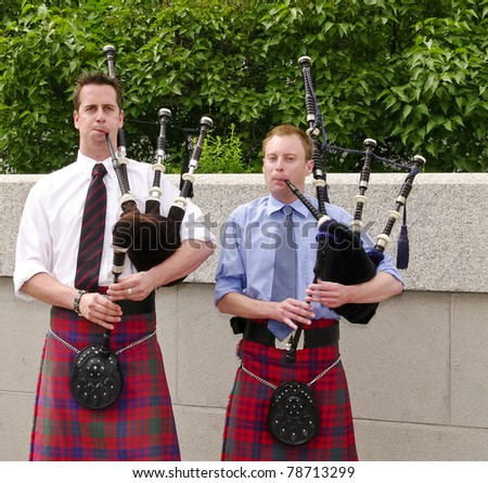 Bagpipe duo in full dress including kilt, playing in Ottawa, Canada.