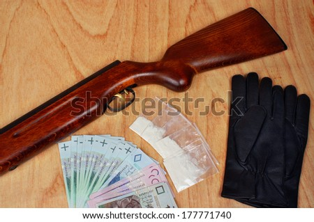 Bags of drugs,  polish money and gun on a wooden table - stock photo