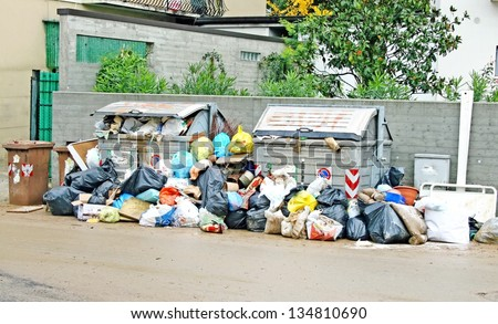 bags of rubbish and waste bins in the middle of the road full of mud - stock photo