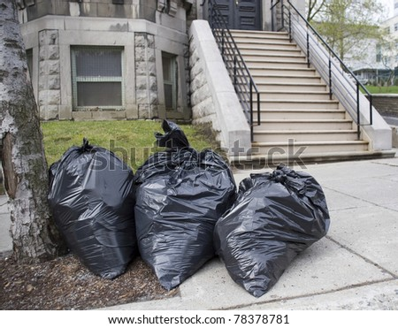 Bags of trash on sidewalk in front of townhouse - stock photo