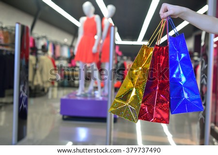 Bags with purchases on a background of a clothing store - stock photo