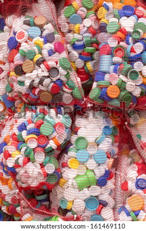 bags with thousands of bottle caps to recycle - stock photo