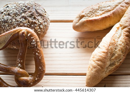 Baguette and whole wheat bread on wooden table.