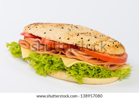 Baguette loaf with ham and vegetables. - stock photo