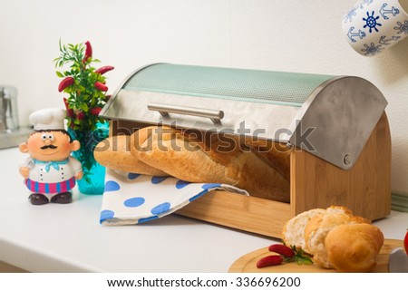 Baguette, lying in a breadbox, made of wood with metal lid - stock photo