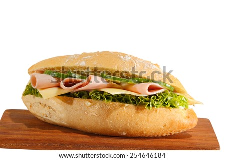 Baguette roll with ham, cheese, lettuce and cucumber slices on a wooden board