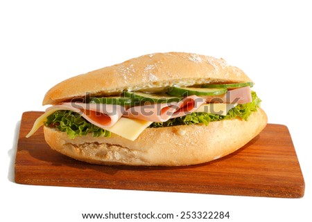 Baguette roll with ham, cheese, lettuce and cucumber slices on a wooden board, isolated