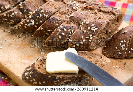 baguette rye bread sprinkled with sesame and poppy seeds on a wooden board - stock photo