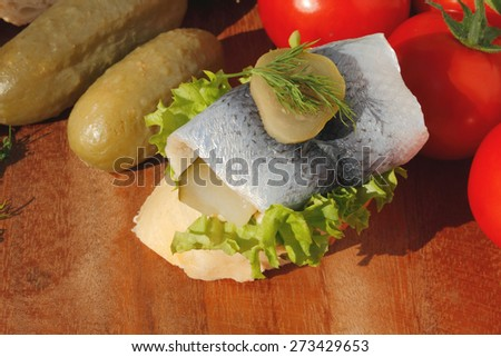 Baguette slice with sour herring, pickled herring, garnished with lettuce, gerkin, dill, tomatoes and onion on a wooden chopping board