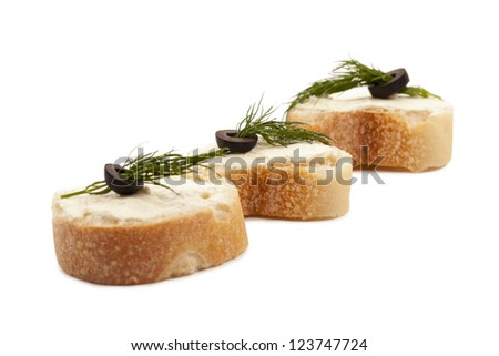 Baguette slices topped with butter dill, and olives
