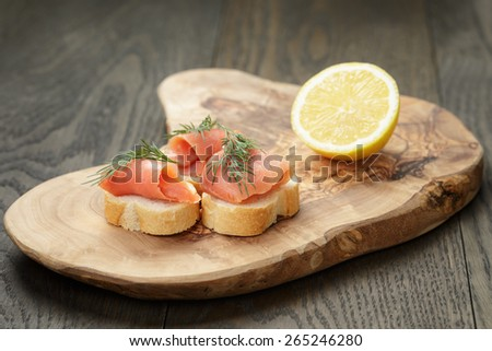 baguette slices with curred salmon and dill on wood table - stock photo