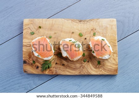 baguette slices with soft cheese and salmon on wood table, vintage toned - stock photo