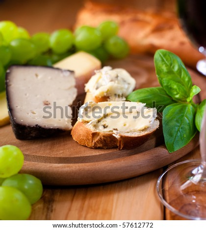 Baguette with brie and manchego cheese on bread board - stock photo