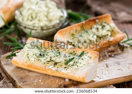 Baguette with Herb Butter and Rosemary on rustic wooden background - stock photo