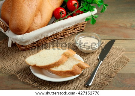 baguettes and vegetables in a wicker basket near the sliced baguette on a plate with sauce on wooden background