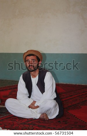 BAHARAK, AFGHANISTAN - JUNE 3: Unidentified Afghan man in traditional dress watches public health lecture in his newly built community center on June 3, 2010 in Baharak, Afghanistan