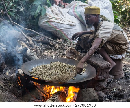 Bahir Dar, Ethiopia - January 18, 2012: Unidentified ethiopian person in poor clothings roasting coffee beans in a large pan placed on a wood fire in Bahir Dar, Ethiopia. Outdoor setting. - stock photo