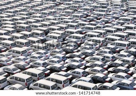Bahrain dockside storage of new cars still covered with white protective sheeting - stock photo