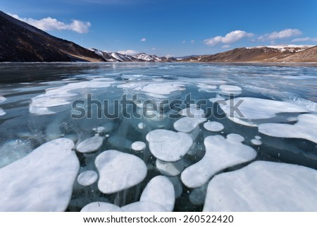 Baikal Lake in winter. View from close range on the transparent ice with white bubbles - stock photo