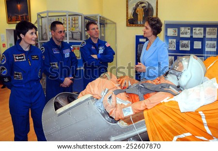 BAIKONUR, KAZAKHSTAN - NOVEMBER 19, 2014: ISS crew Cristoforetti (left), Shkaplerov (center) and Virts (right) listen to Space Museum Director next to Vostok spacecraft ejection seat with mannequin - stock photo