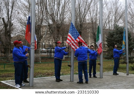 BAIKONUR, KAZAKHSTAN - NOVEMBER 13, 2014:  ISS Expedition 42/43 prime and backup crewmembers raise the flags of Russia, the U.S., Italy and Kazakhstan during traditional flag raising ceremony - stock photo