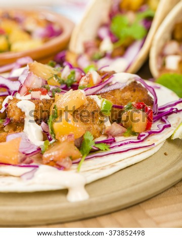 Baja Fish Tacos - Soft shell tacos filled with seasoned fried white fish served with red cabbage, pineapple salsa, chunky guacamole and creamy Baja style sauce. - stock photo