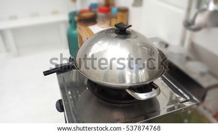 Bake cooking in stainless steel pan has cover to close it on the stove in kitchen, Background around are blur.