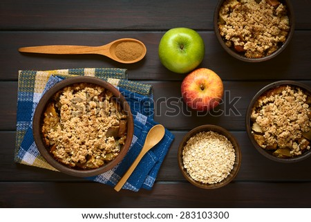 Baked apple crumble or crisp in rustic bowls, spoonful of cinnamon powder, fresh apples and raw rolled oats on the side, photographed overhead on dark wood with natural light - stock photo