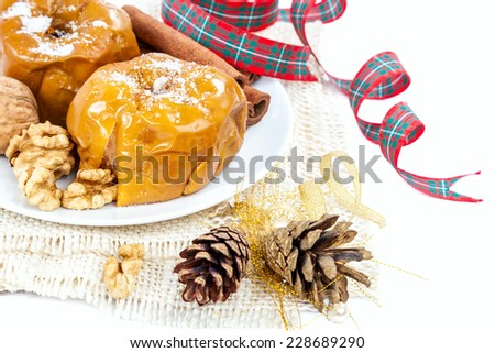 Baked apples with nuts and cinnamon on white background. - stock photo