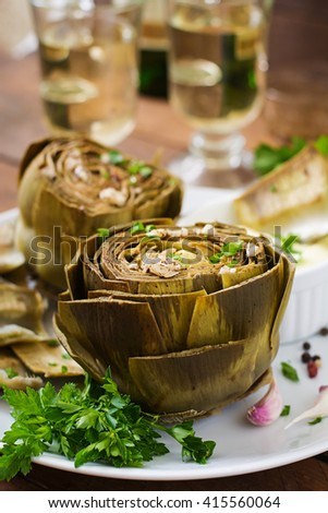 Baked artichokes cooked with garlic sauce, mustard and parsley - stock photo