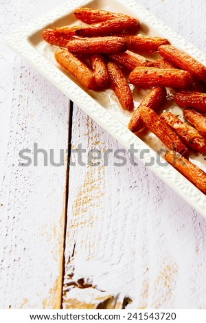 Baked baby carrots with oregano on white wooden background. Selective focus. - stock photo