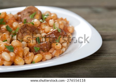 Baked beans and sausages in white plate over old rustic wood background - stock photo