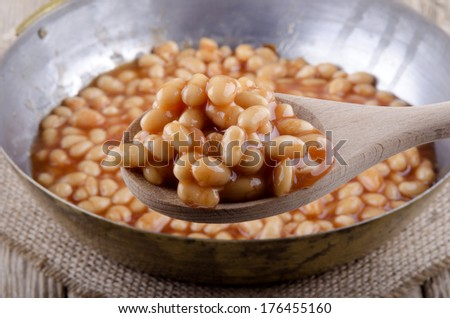 baked beans in a pan and wooden spoon  - stock photo