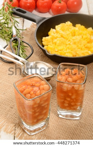baked beans in a shot glass, scrambled eggs in a cast iron pan, fresh tomatoes, rosemary and herbal scissor  - stock photo